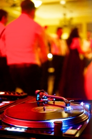 A vinyl turntable with Dj hands with people dancing in the background at a wedding event in California USA