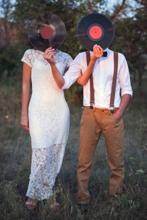 Creative Unrecognizable Funny Couple Have Romantic Date At Forest. Conceptual Image of Man And Woman Hold A Vinyl Record Discs On Their Faces